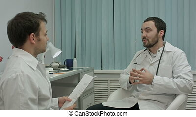 Male doctor and young intern in a good mood talking about new medical researchs