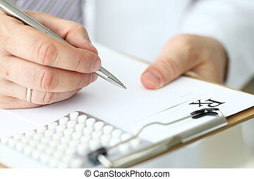 Male doctor arm filling out prescription form