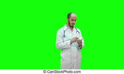 Male doctor attentively reading medicine label of a bottle of pills on a Green Screen, Chroma Key.