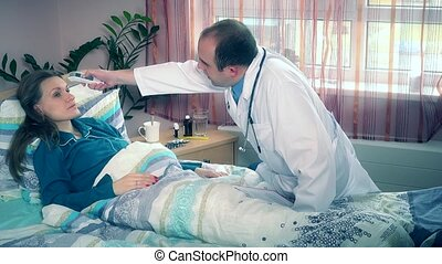 Male doctor check female patient temperature and make notes