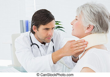 Male doctor examining a senior patient's neck