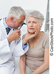 Male doctor examining senior patient's ear