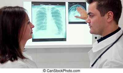Male doctor explaines something on x-ray to his female colleague