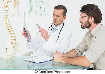Male doctor explaining spine x-ray
