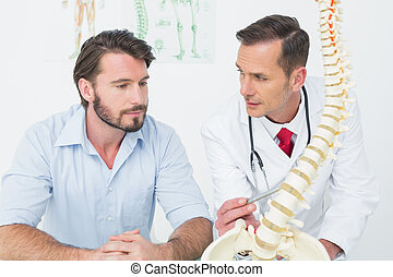 Male doctor explaining the spine to