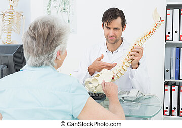 Male doctor explaining the spine to a senior patient