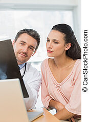 Male doctor explaining x-ray report to a patient