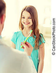 male doctor giving toothbrush to smiling girl
