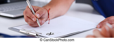 Male doctor hand write prescription at office worktable