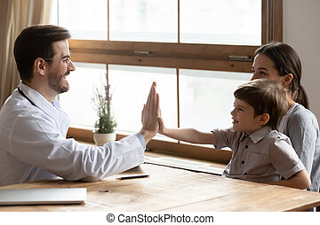Male doctor have fun greeting with little patient