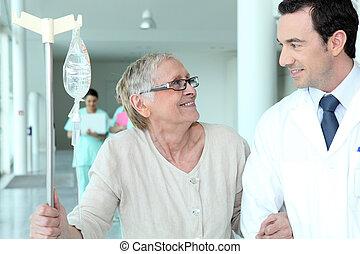 Male doctor helping elderly patient