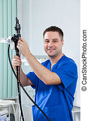 Male doctor holding an endoscope.