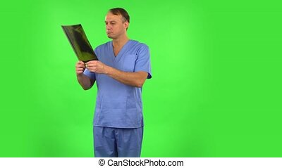 Male doctor in blue coat reviewing x-ray pointing on snapshot and explains. Handsome man dressed in blue medical uniform on a green screen in the studio