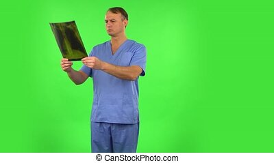 Male doctor in blue coat reviewing x-ray pointing on snapshot, explains and shows thumb like. Handsome man dressed in blue medical uniform on a green screen in the studio