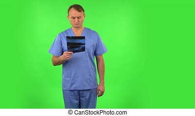 Male doctor in blue coat reviewing x-ray pointing on snapshot. Handsome man dressed in blue medical uniform on a green screen in the studio