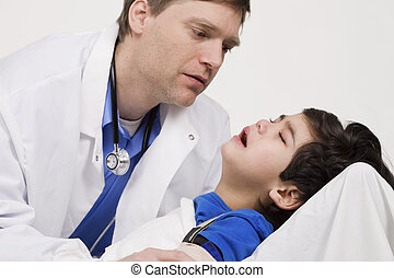Male doctor in early forties comforting five year old disabled patient during office visit