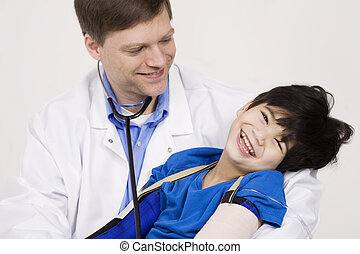 Male doctor in early forties holding five year old disabled...