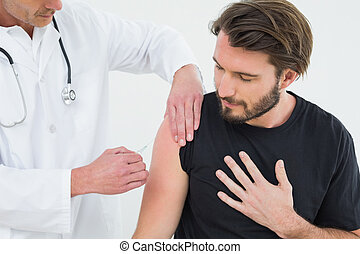 Male doctor injecting a young male patient's arm over white...