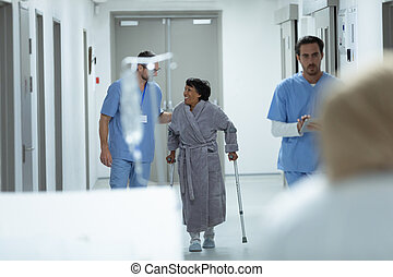 Male doctor interacting with disabled female patient in the corridor