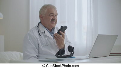 male doctor is talking by speakerphone in mobile phone in his office in clinic, recording voice message, consulting patient by cellphone, helping to sick people