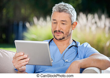 Male Doctor Looking At Tablet PC