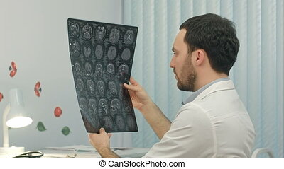 Male doctor looking at x-ray picture in the medical office