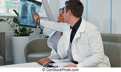 Male doctor points on the x-ray at the hospital
