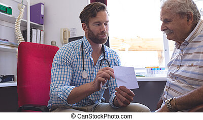 Male doctor prescribing medicine to senior man in clinic
