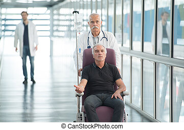 male doctor pushing patient with wheelchair in the hospital corridor