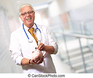 Male Doctor Putting Coins In A Piggy Bank