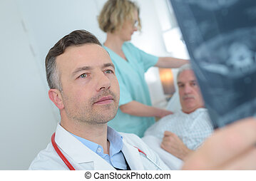 male doctor reviewing patients x ray at hospital