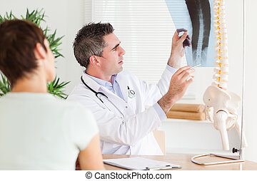 Male Doctor showing a female patient a x-ray