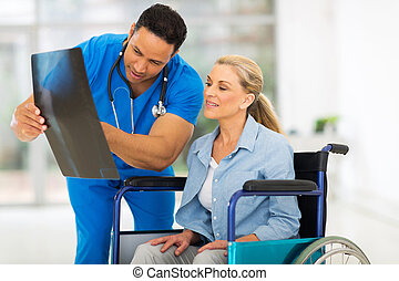 male doctor showing x-ray report to senior disabled patient