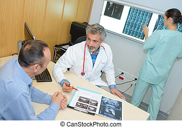 male doctor showing xray to patient nurse in the background