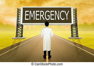 male doctor standing on road and looking with large sign of emergency