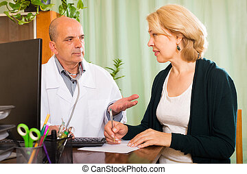 Male doctor talking with mature patient