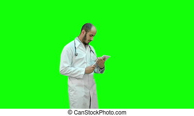 Male doctor using digital tablet on a Green Screen, Chroma Key.