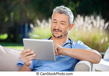 Male Doctor Using Digital Tablet While Sitting On Couch