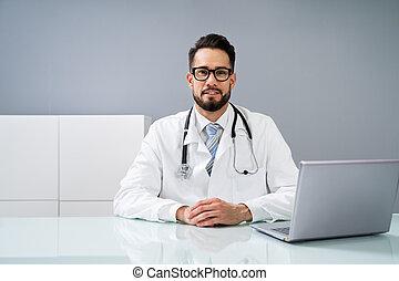 Doctor Using Laptop At Desk