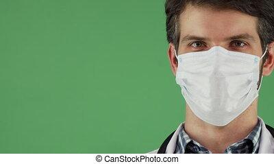 Male doctor wearing medical mask smiling joyfully - Sliding...
