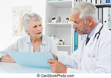 Male doctor with female patient reading reports