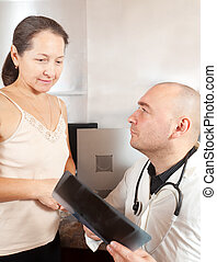 doctor with patient looking x-ray
