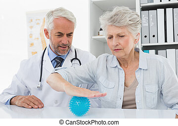Male doctor with senior patient using stress buster ball