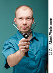 male doctor with stethoscope looking at camera on blue background