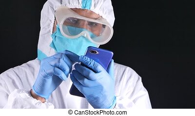 male doctor's hand in protective gloves using a smartphone.