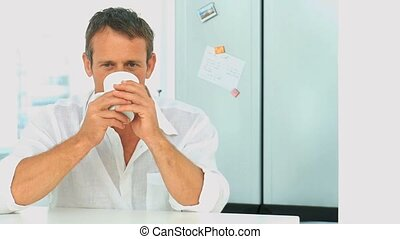 Male drinking a cup of tea in his kitchen