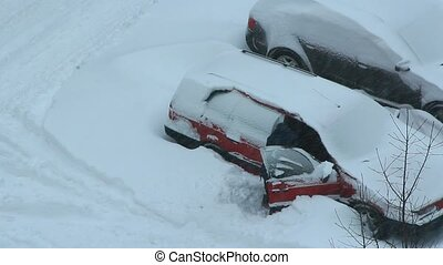 Male driver trying to free his car from snowy captivity....