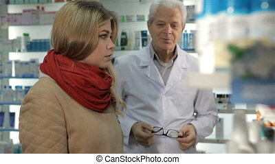 Male druggist consultates female customer at the drugstore