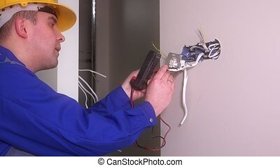 Male electrician checking outlet with special equipment. Man with helmet