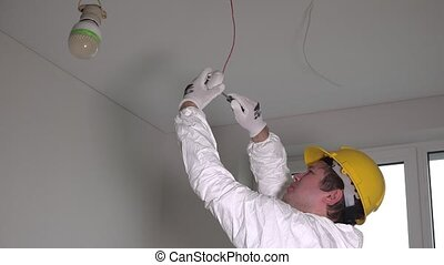 Male electrician installing fire smoke alarm with...